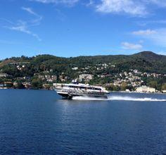 Hydrofoil boat races across Lake Como on its way to Como's dock. Lake Como, Italy