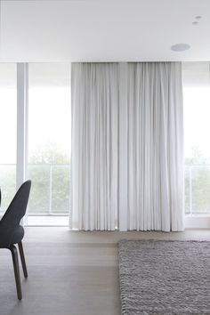 Floor to ceiling soft drapes and oatmeal woven carpet for minimal, understated bedroom luxury   Rietveld Bouwprojecten