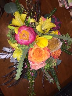 Vibrant, saturated colors of rich yellows, fuchsia, and sunset hues. Peony, Free Spirit rose, yellow asiatic lily, yellow calla, Banksia protea, euphorbia, boronia.
