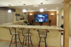 sectional couch with bar stools behind a half wall capped with granite bar top doubles the number of friends who can have a great view of the game