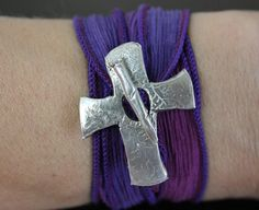 Silk Wrap Bracelet ~ This hand carved Cross and Nail depicts God's love for us.  The two piece toggle is hand carved and cut, and are not made using a commercial mold.  This cross toggle is hand crafted from reclaimed silver. This shimmering toggle is interlaced with a hand dyed silk ribbon with cool hues of lavender and purple that wraps end over end around your wrist. The gentle sari wrap is generous, and flowing in grace and comfort.