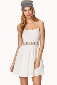 A crepe woven dress featuring a crocheted lace panel at the waist. Round neckline. Adjustable spa...