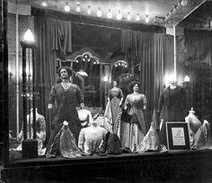 Etalage van de winkel in dameskleding Maison de Vries, Leidsestraat 89-93. In de elektrisch verlichte etalages staan etalagepoppen met jurken en worden blouses geëtaleerd. Amsterdam 1909.