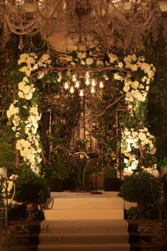 Romantic wrought iron, woven-branches, bursting white rose blossoms and candlelight. Lewis Miller.