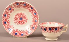 """Red and Blue Stick Spatter Ironstone China Child's Teacup and Saucer. Saucer 4-1/4"""" diameter. Condition: Very Good."""