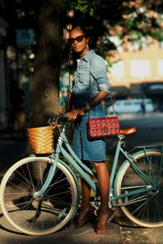the bike, the hair, the glasses, the flats, the toes pointed. and throw in the bag. the denim, not so much, but on her it looks great.