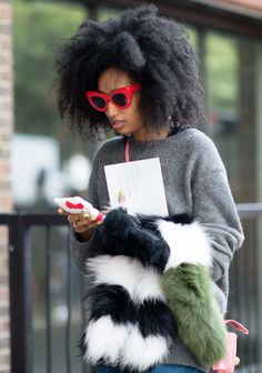 Julia Sarr Jamois Proof that if you're in a sweater in jeans, all you need is a great pair of glasses and a furry thing to hold and you're street-style gold.  Photo: YoungJun Koo/I'M KOO