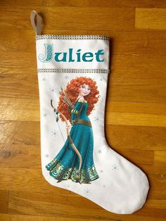 """Princess Merida Christmas Stocking  Surprise your little one with a personalized princess Merida stocking this Christmas! These stockings are hand made here in the USA. They are 100% cotton and are lined with a beautiful white satin lining. They measure 17"""" tall by 10"""" wide. I personally apply the iron-on art and rhinestone trimmings. Each snowflake also has crystal colored rhinestones. This stocking is 100% hand made from start to finish.   Purchase one today at www.labelmybaby.com!"""