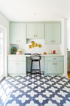 mint kitchen cabinets with gold hardware and black and white tiled floors / sfgirlbybay