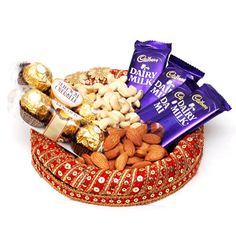 This is a beautiful decorative round shaped tray. The tray comes with 3 Dairy Milk, 6 pieces Ferrero Rocher, 100 gms Kaju and 100gms Almond . Your loved ones will definitely be delighted to have these scrumptious chocolates and dryfruits. Send this tray to your loved ones to India through Giftblooms.com. You can also opt for other Gifts to India with this tray.