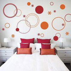 painting orange and red circles on white wall in bedroom