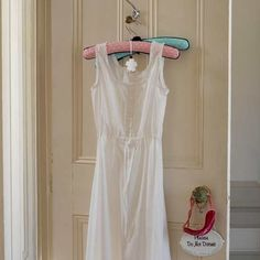 White dress on a padded hanger hanging on a door