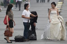 No mask for the bride during a prewedding shoot at Singapore's Marina Bay Waterfront Thursday. The Pollutant Standards Index hit the highest level on record—371, with 300 designating 'hazardous—only to exceed that mark Friday.
