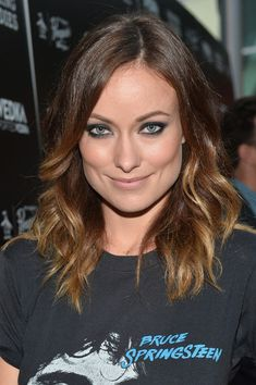 Olivia Wilde makes her concert T-shirt stylish with wavy curls, bold smoky eyes and muted lips.