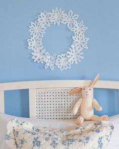 """Paper snowflakes are breathtaking when seen hovering in midair. For a simple yet sophisticated wall decoration, snowflakes were cut from paper using our template, then affixed to the wall using poster putty in the shape of a circle to form a """"wreath.""""    Get the Snowflake Template"""
