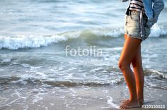 Girl's legs standing in the seashore