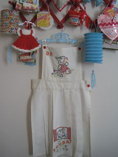Vintage Embroidered Apron on Red Accordion Rack