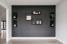 White study with a dark gray accent wall with shelves and decor Dark Accent Walls, Dark Grey Walls, Accent Walls In Living Room, Accent Wall Bedroom, Black Walls, Dark Grey Feature Wall, Grey Wall Color, Accent Wall Colors, Wall Paint Colors