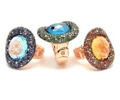 Rodney Rayner Via Roma Oval rings (left to right): pavé blue sapphire, diamond and blue topaz ring set in red gold; pavé tsavorite, blue sapphire, diamond and blue topaz ring set in red gold; pavé orange sapphire, champagne diamond, diamond and citrine ring set in red gold.