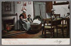 Een zittende vrouw met kanten muts, hele rode doek, kraplap, boormouwtjes en licht schort. Een klein meisje met pluummuts, jurkje met lange mouwen en schort. Een baby in een rieten schommelwieg met wiegekleed. Open vuur in de schouw met tegeltableau's, bedsteegordijnen en een hoekkastje. Een tafel met zeiltje, waaromheen drie stoelen, twee zgn. suikerpotstoelen en een met spijltjes. Op de tafel een olielamp. Houten planken vloer. 1900-1904 #Utrecht #Spakenburg