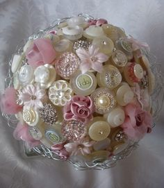<3 button bouquet-I just pinned this to remind myself how putting mismatched buttons together can be beautiful. Looks like they have some ribbon and flowers glued on top of some of the buttons, too.