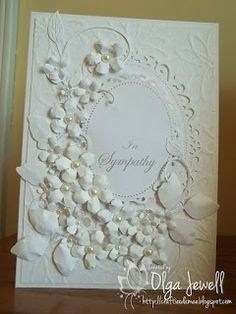 A Stampin Up embossing plate; spellbinders Floral Ovals and Foliage; Cherry Lynn's Fanciful Flourish; and Memory box fancy Blossoms.  Pearls were added to the center of each flower.