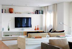 A luz natural entra suave na sala deste apartamento. Os raios de sol são filtrados pela persiana branca que cobre a porta-janela, com 5 m de largura. O xale de linho faz o acabamento. Projeto da arquiteta Paula Magnani