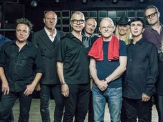 "Tony Visconti (third from left), Mick ""Woody"" Woodmansey (fifth from left) and Holy Holy perform in New Brunswick on April 6. (Photo: Courtesy of the Awareness Group)"