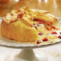 Holiday Brie en Croute -  1 egg  1 tablespoon water  All-purpose flour  1/2 of a 17.3-ounce package Pepperidge Farm® Puff Pastry Sheets (1 sheet), thawed  1/2 cup apricot preserves or seedless raspberry jam  1/3 cup dried cranberry  1/4 cup toasted sliced almond  1 (13- to 16-ounce) Brie cheese round  1 package (13 ounces) Pepperidge Farm® Quartet Cracker Assortment