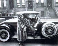 A beautiful Black couple strike a pose wearing matching fur coats. West 127th Street, Harlem NYC, 1932. James Van Der Zee, photographer.
