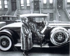 An African American couple strike a pose wearing matching racoon fur coats. West 127th Street, Harlem NYC, 1932. James Van Der Zee, photographer.