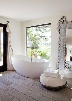 Wood tile | large ornate mirror | white walls | black bronze door and window frame | tub