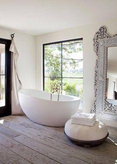 Wood tile | large ornate mirror | white walls | black bronze door and window frame | tub