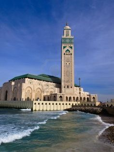 View of Hassan II Mosque and Minaret in Casablanca, Morocco with waves crashing its walls Stock Photo