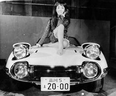 """""""Bond Girl"""" Mie Hama sits on the hood of one of two Toyota 2000GT roadsters built for the film """"You Only Live Twice"""" - Sean Connery was too tall to fit in the regular hardtop version."""