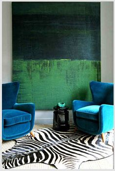 This large abstract painting hung almost to the floor defines the space with the 2 armchairs and creates intimacy.