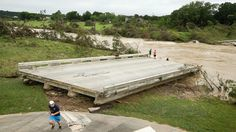 Firefighter Killed as Flooding Wreaks Havoc in Texas, Oklahoma PHOTO: Dustin McClintock, of Wimberley,, Brandon Bankston, of Blanco, Hesston Krause, of Smithson Valley, look at the Fischer Store Road bridge over the Blanco River near Wimberley, Texas, which was destroyed in a flood on Sunday May 24, 2015.