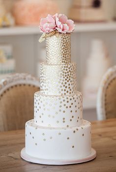 Pretty gold sequin white wedding cake with pink flowers