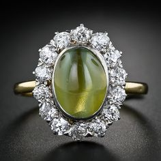A honey-green Chrysoberyl cats-eye, weighing about 4.00 carats, and with excellent chatoyancy it stares right back at you from within a sparkling halo of bright-white old mine-cut diamonds. This entrancing nineteenth century ring is finely crafted in 18 karat yellow gold with a platinum top.
