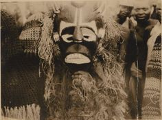 Nigeria, close-up of Ibo adult male wearing shaggy masquerade costume, painted mask. Small group of adult males at left and right, wearing masks of knitted material. Small group of males looking on in background. Medium: Gelatin silver print; sepia.