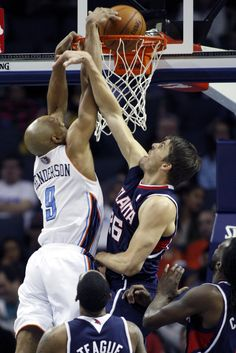 Charlotte Bobcats guard Gerald Henderson, left, dunks over Atlanta Hawks guard Kyle Korver in the second half of an NBA basketball game in Charlotte, N.C., Monday, Nov. 11, 2013. Atlanta won 103-94. (AP Photo/Nell Redmond)