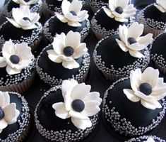 Cupcakes....would taste better with white buttercream and black flowers...love the silver sprinkles too.  Could core out the centers and fill with Oreo Cookie filling...YUM and black & white!