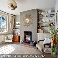 Ein Highlight in diesem Wohnzimmer ist der große Sonnenspiegel über dem Ofen. In Kombination mit verschiedenen Retro-Möbeln und ausgewählten Dekoelementen  …