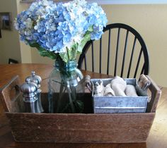 Simple dining table centerpiece with salt/pepper, cloth napkins and a flower arrangement.