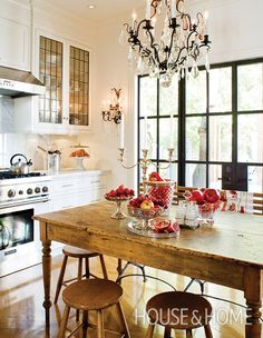 An antique chandelier and matching wall sconces give this kitchen an intimate feel. | Photographer: Ted Yarwood | Designer: Sharon Mimran