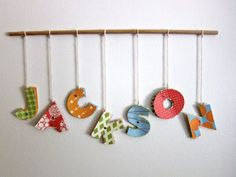 Cut out letters from cardboard, cover with paper or fabric, hang them from string on the wall or the door (so the little ones know where they sleep when they visit). They can take it home when they leave.