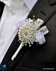 Our most popular boutonniere design, featuring a single brooch, fabric flower and rhinestone garnishes on a stem. The photos show a variety of color examples. We're happy to make it in any colors you choose. We will make your boutonniere to match your bouquet or your wedding color scheme. This design can be paired with any of our bridal bouquets.