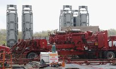CONSOL Energy fracking at Pittsburgh Airport - A small fleet of truck-mounted pumps flow a mixture of fracking sand and water to the well heads. The silos contain fracking sand.