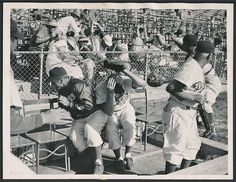 This is a 1953 vintage press photo issued by International News Photos showing some Brooklyn Dodgers diving for cover during a Spring Training game at Vero Beach.  George Shuba, Ben Wade and coach Jake Pitler cover up.  Is that Roy Campanella in his catcher gear?