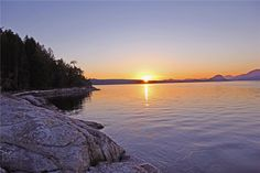 The sun sets over Cortes Island - from Cabana Desolation Eco Resort in Desolation Sound, British Columbia.